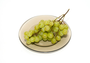 Green grapes on the plate isolated on white.