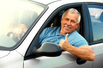 Smiling happy elderly man  in the new car.
