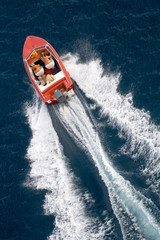 family into fast driving boat on the sea