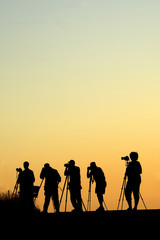 Silouette of five photographers lined up shooting photos