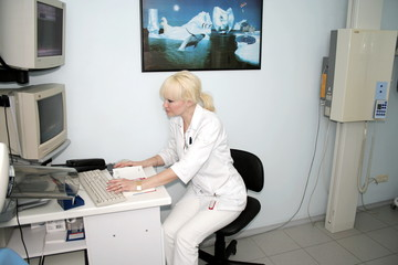 Woman-radiologist processing x-ray pictures on computer