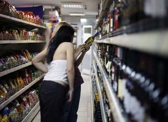 Two girls choose a wine in a supermarket