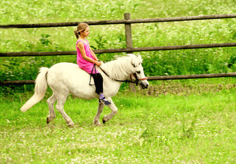 Little girl in pink dress galloping on her white pony