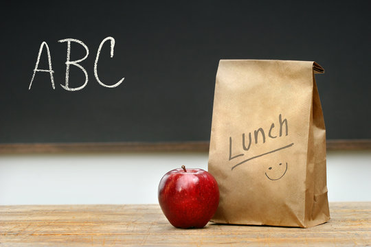 Paper lunch bag on desk with apple