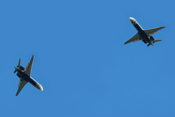 two flying planes isolated over blue sky