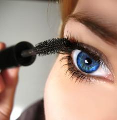 blue eye applying mascara
