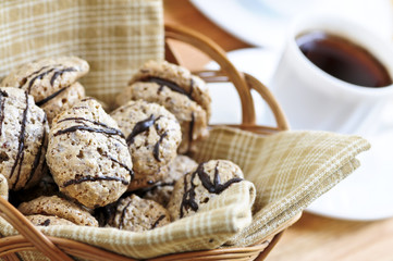 Fresh sandwich cookies in a basket and espresso coffee