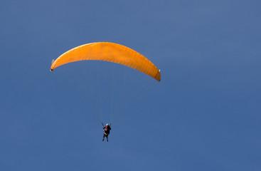 parapente orange sur ciel bleu