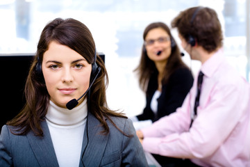 Customer service team working in headsets, smiling
