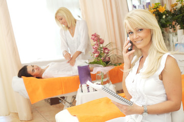Beautician recieving phone calls in the beauty shop.