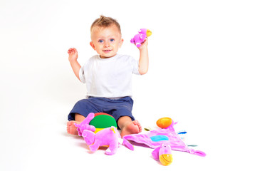 One year old baby boy enjoys playing with toys.