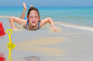 Happy girl splashing in ocean water