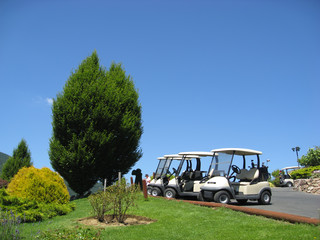 empty golf carts at a golf club below beautiful blue sky