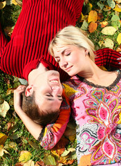 young beautiful couple is laying on the autumn grass