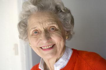 Portrait of attractive senior woman standing by front door