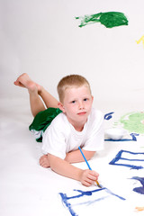 Boy paints pictures on white paper.