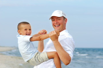 Beautiful adult father playing with young son on beach