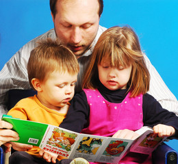 Father with his children reading a pictures book