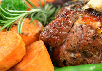 Roast lamb with garlic, carrots, beans and pumpkin.