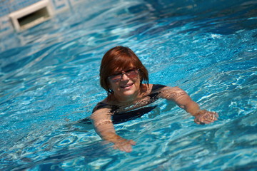 Happy active senior woman ( 60s ) swimming in pool