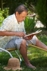 Healthy looking aged man is his late 70s sitting in garden