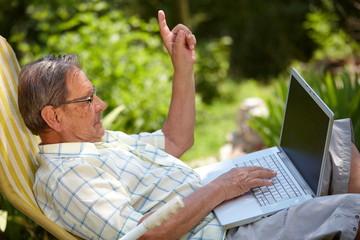 Healthy senior man in his elderly 70s using laptop computer