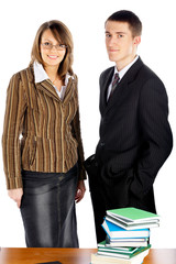 businessman and businesswoman standing near the table with books