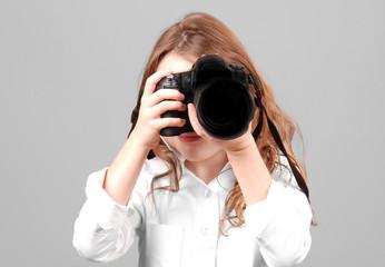 Young girl aiming digital SLR camera