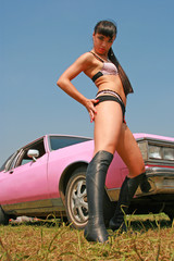 The girl poses in front of the beautiful car