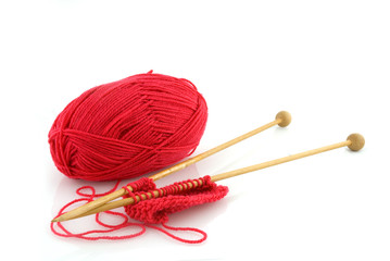 knitting with red wool and wooden needles