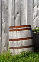 barrel on grass near a wood wall