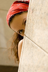 woman in red kerchief looking behind a wal
