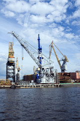 Large construction cranes in shipyard.