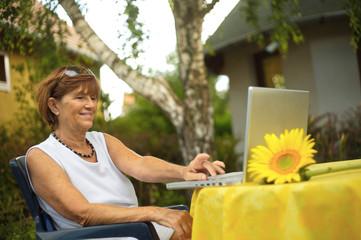 Modern senior woman sitting using a laptop computer.