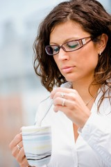 Young businesswoman drinking coffee and thinking.
