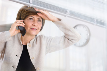 Senior businesswoman looking through office window
