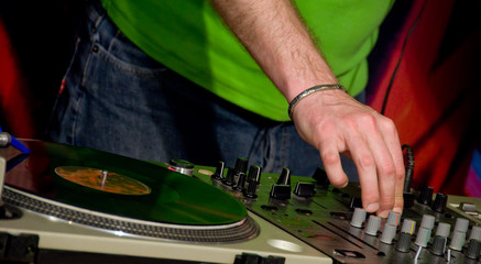 A detail of a gramophone disc with a DJ´s hand