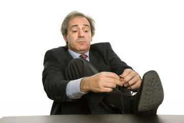 mature business man tying his shoe in a desk