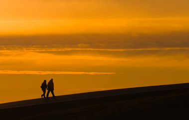 Foto auf AluDibond Wuste Sandig silhouettes of two walking tourists on sunset sky background
