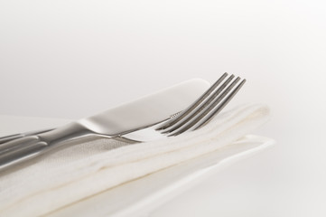 close up view of fork knife and napkin resting on plate