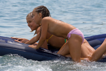 two girls of teenager float on an air-bed in the sea
