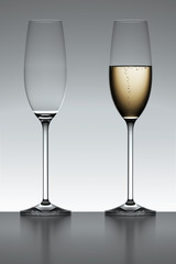 Full and empty champagne flute iover a gray background.
