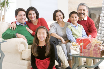 Family Sitting Around A Coffee Table And Christmas Gifts