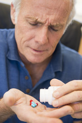 Senior Man Pouring Pills Out Of Bottle
