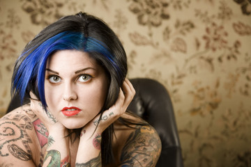 Pretty young woman with many tattoos in a leather chair