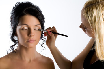 Young attractive woman while making-up