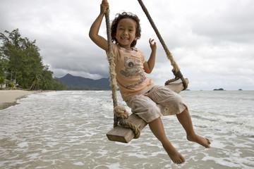 Mädchen auf Schaukel beim Meer