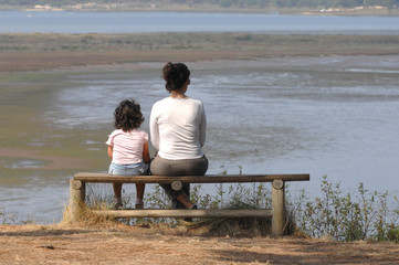 Mother and daughter sitting on a park