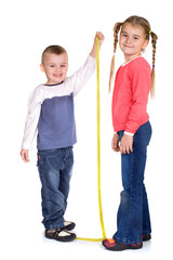 litlle boy measuring her sister's height