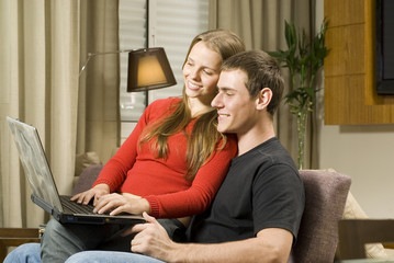 Young couple at home working on  computer. Horizontal.